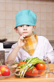 Thoughtful little cook Stock Images