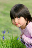 Thoughtful Little Girl. Face of a little girl sitting on the grass in spring next to some bluebells Stock Photos
