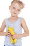 Thoughtful little girl with a banana in his hand Stock Photo