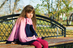 Thoughtful little girl on the bench. Royalty Free Stock Photography
