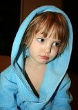 Thoughtful little girl in blue bathrobe with hood stock photos