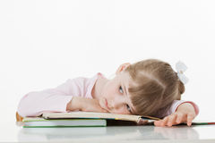 Thoughtful little girl with a books Royalty Free Stock Photos