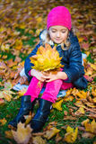 Thoughtful little girl with bouquet of maple leaves in autumn pa Royalty Free Stock Image