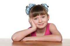 Thoughtful little girl at the desk Stock Photos