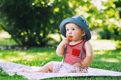 Baby eating strawberries on green nature background. Stock Photos