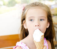 Thoughtful little girl eating ice cream Stock Images