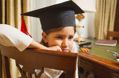 Thoughtful little girl in graduation hat posing on chair Royalty Free Stock Image