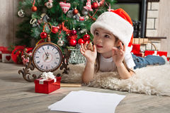 Thoughtful little girl in hat writes letter to Santa Claus. Little girl writes letter to Santa and dreaming about gifts Stock Photography