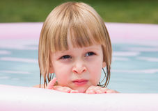 Thoughtful little girl in inflatable pool Royalty Free Stock Image