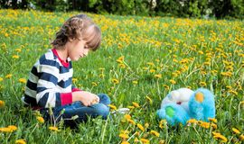 Thoughtful little girl on the lawn Royalty Free Stock Photography