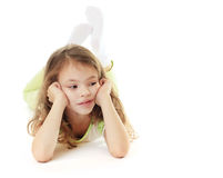 Thoughtful little girl lies Royalty Free Stock Photo