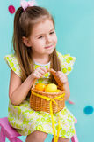 Thoughtful little girl with long blond hair holding wicker basket with yellow eggs stock images