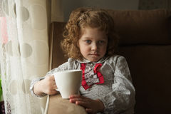 Thoughtful little girl with a mug Royalty Free Stock Image