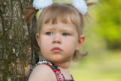 Thoughtful little girl near the tree Stock Image