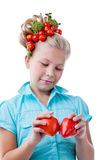 Thoughtful little girl puts heart of tomatoes Royalty Free Stock Images