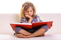Thoughtful little girl reading Stock Images