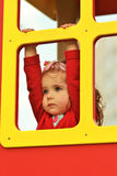 Thoughtful little girl in red looking in the distance out of a window of a colorful wooden house Royalty Free Stock Photos