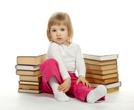 Thoughtful  little girl sitting among books Royalty Free Stock Photos