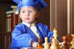 Thoughtful little girl in suits play chess Royalty Free Stock Photography