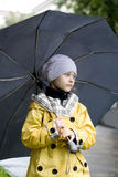 Thoughtful little girl in a yellow raincoat Stock Image
