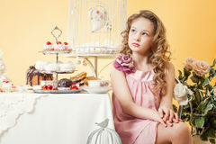 Thoughtful little lady posing at table with cakes Royalty Free Stock Photos