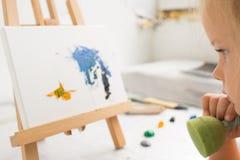 Thoughtful little painter in art studio stock photo