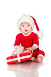 Thoughtful little Santa Claus with presents. Royalty Free Stock Photos