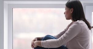 Thoughtful lonely african woman sit on sill look through window
