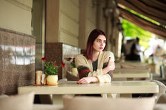 Thoughtful lonely woman in cafe on summer area Stock Image