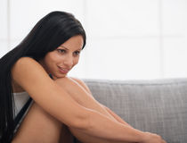Thoughtful long hair girl sitting on couch Stock Images
