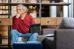 Pleasant elderly man holding his chin Royalty Free Stock Images