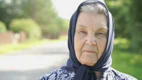 Thoughtful look of a serious old woman. Close-up stock footage