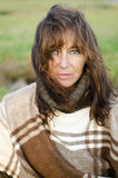 A thoughtful looking mature woman in her forties. A thoughtful looking mature woman in her forties with brown hair and green eyes and wearing a brown poncho Royalty Free Stock Images