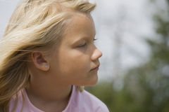 Thoughtful looking young girl outdoors Stock Photos