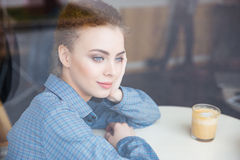 Thoughtful lovely young woman drinking coffee and thinking in cafe Royalty Free Stock Photos