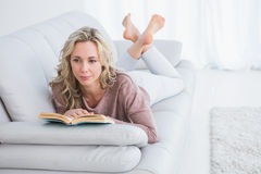 Thoughtful lying on couch reading book Stock Photography