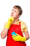 Thoughtful male in an apron with a sponge Royalty Free Stock Photos
