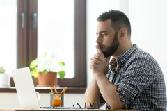 Thoughtful male considering business problem solution. Concerned millennial male worker looking at laptop screen thinking about problem solution, startup project stock photography