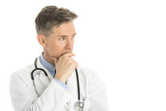 Thoughtful Male Doctor Looking Away. While standing against white background Royalty Free Stock Images