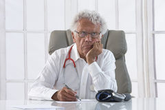 Thoughtful male doctor. Portrait of an overworked doctor rubbing his head, looking totally stressed out Stock Image