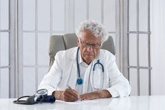Thoughtful male doctor. Portrait of an overworked doctor rubbing his head, looking totally stressed out Stock Images