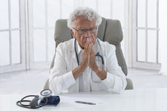 Thoughtful male doctor. Portrait of an overworked doctor rubbing his head, looking totally stressed out Royalty Free Stock Photography