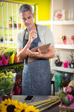 Thoughtful male florist looking reading clipboard Royalty Free Stock Images