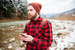Thoughtful male hiker holding smartphone. With river on background Royalty Free Stock Images
