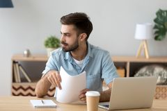 Thoughtful male look in distance working at office table royalty free stock images
