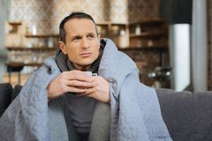 Thoughtful male person being sick at home. Medical treatment. Concentrated man wrinkling forehead and pressing lips while holding cup with coffee in both hands Royalty Free Stock Photos