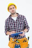 Thoughtful male repairman writing on clipboard. Over white background Royalty Free Stock Photo