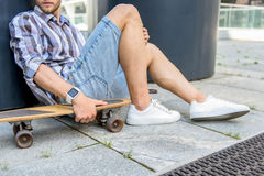 Thoughtful male skater relaxing on street. Pensive young man is resting with skate outdoors. He is sitting and leaning on column with relaxation Royalty Free Stock Images