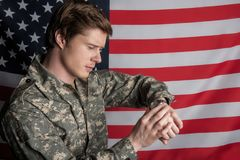 Meditative young officer checking time royalty free stock images