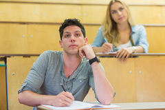 Thoughtful male student during class. At the lecture hall Royalty Free Stock Photos